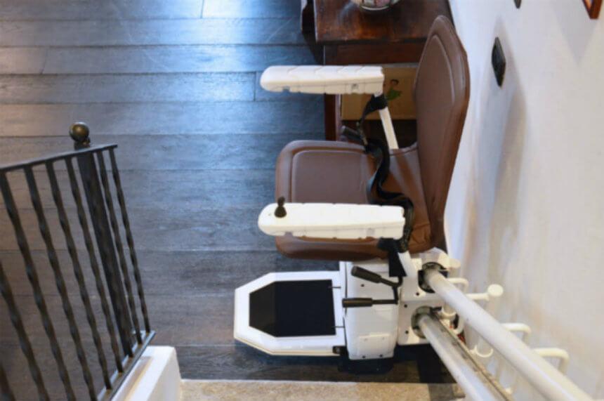 Montascale per disabili per scale curve modello infinity con comoda pedanetta poggiapiedi